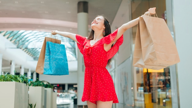 Ragazza in posa con borse della spesa