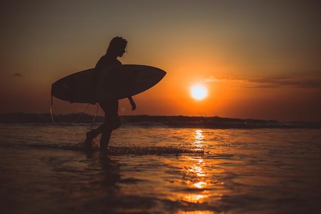 Ragazza in posa con un bordo al tramonto