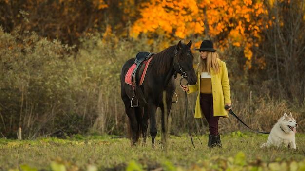 Ragazza in posa con un cavallo e un cane