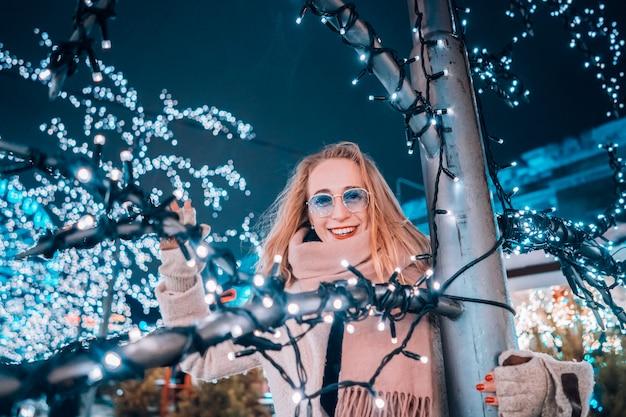 Ragazza in posa sullo sfondo di alberi decorati