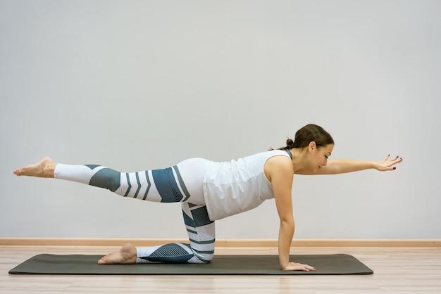 Ragazza in posizione di stretching. concetto esile perfetto di stile di vita del corpo di misura di sanità della curva del corpo sportivo della ragazza