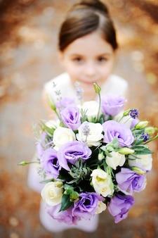 Ragazza in possesso di un bouquet da sposa di fiori bianchi e viola
