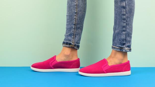 Ragazza in scarpe da tennis rosse e jeans strappati che cammina sul pavimento blu. stile sportivo.