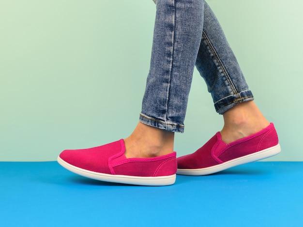Ragazza in scarpe da tennis rosse e jeans strappati che cammina sul pavimento blu