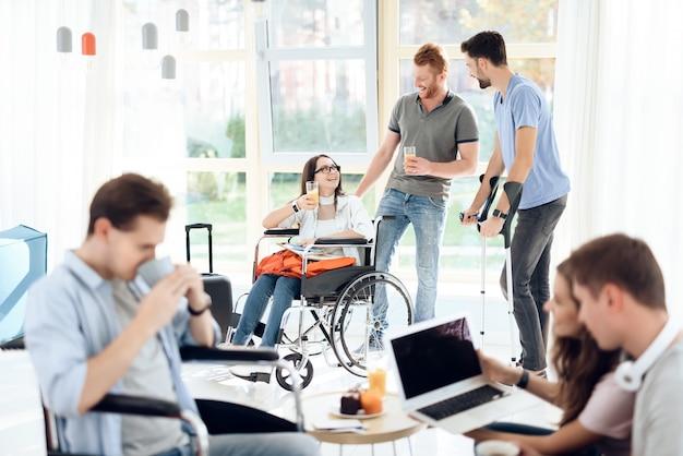 Ragazza in sedia a rotelle e disabili sono in piedi nel corridoio dell'aeroporto.