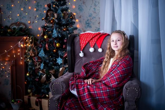 Ragazza in sedia avvolta in una coperta, dell'albero di natale