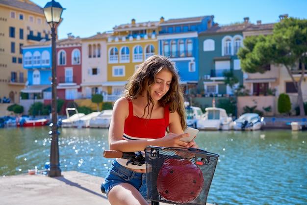 Ragazza in sella a una bici elettrica pieghevole in un porto turistico mediterraneo
