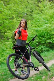 Ragazza in sella a una bicicletta nel bosco