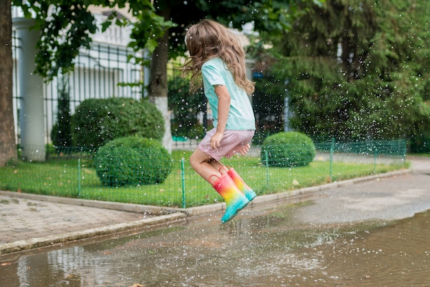 Ragazza in stivali di gomma arcobaleno che salta in pozzanghere vicino alla casa