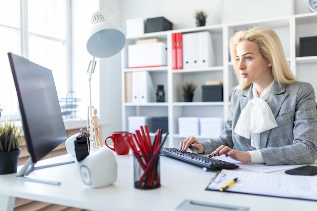 Ragazza in ufficio che lavora con il computer e i documenti.