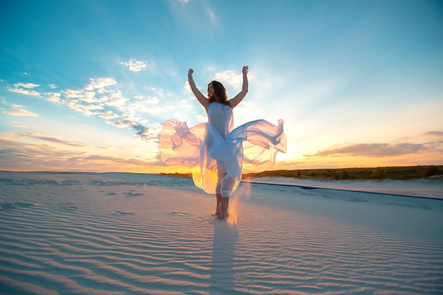 Ragazza in un abito bianco vola balla e pone nel deserto di sabbia al tramonto