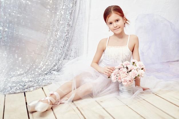 Ragazza in un abito da ballo bianco e scarpe, bella