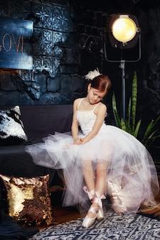 Ragazza in un abito da ballo bianco e scarpe, capelli rossi