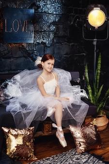 Ragazza in un abito da ballo bianco e scarpe
