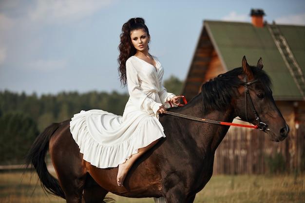 Ragazza in un abito lungo a cavallo, una bella donna a cavallo in un campo in autunno.