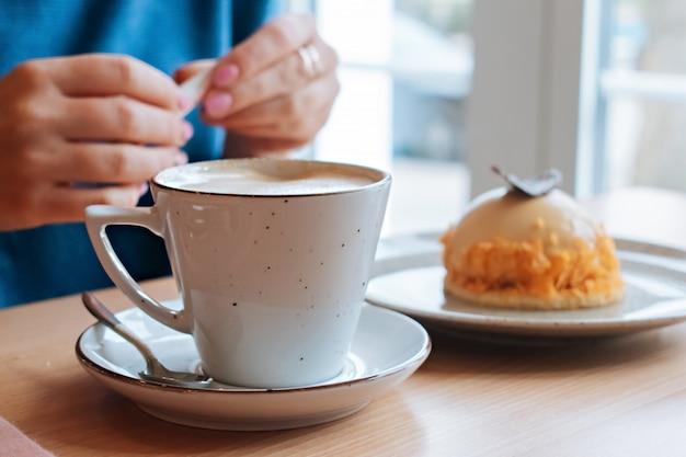 Ragazza in un caffè con caffè e torta