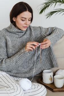 Ragazza in un caldo maglione grigio lavora a maglia seduto su un divano in un accogliente hygge interno