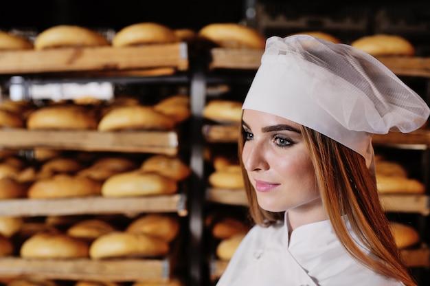Ragazza in un cappello bianco in un forno