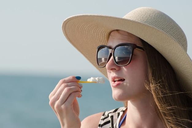 Ragazza in un cappello che mangia un cucchiaio di gelato