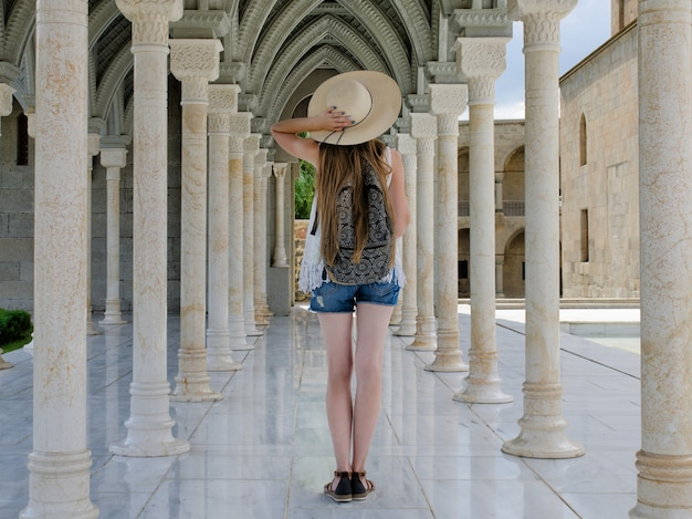 Ragazza in un cappello con uno zaino in piedi tra le colonne