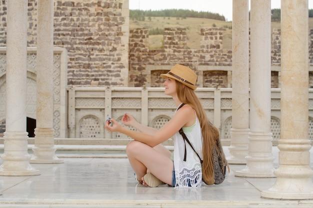 Ragazza in un cappello con uno zaino seduto nella posizione del loto