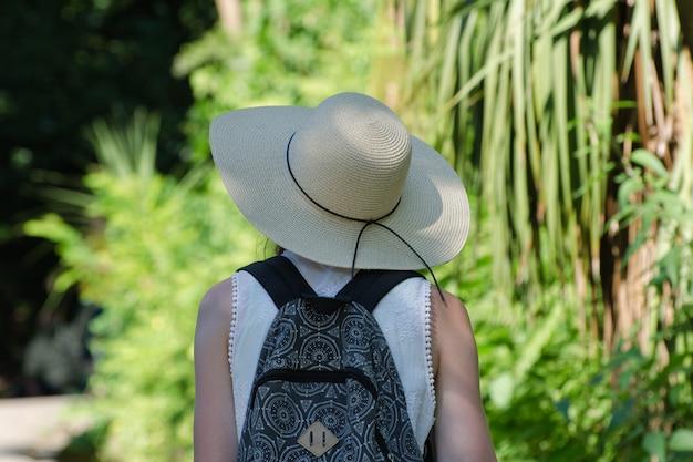 Ragazza in un cappello e uno zaino si trova in un parco. vista posteriore