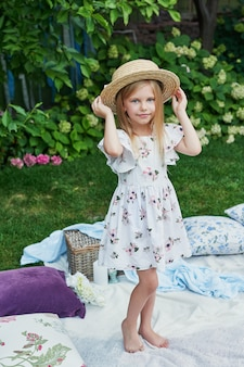 Ragazza in un cappello in giardino a un picnic