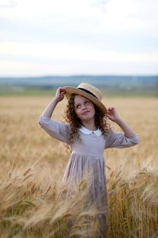 Ragazza in un cappello in un campo di grano