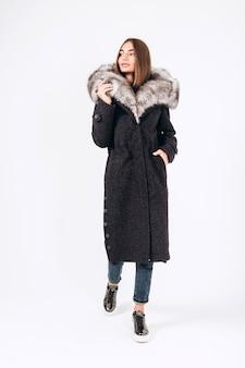 Ragazza in un cappotto invernale con un collo di pelliccia su uno sfondo bianco