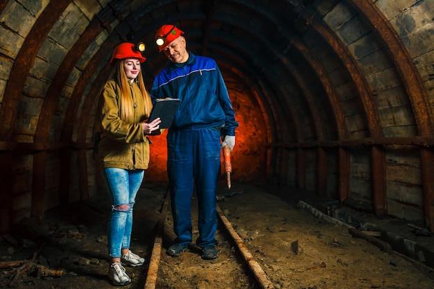 Ragazza in un casco rosso che sta con un minatore in una miniera di carbone. discussione sul piano aziendale.