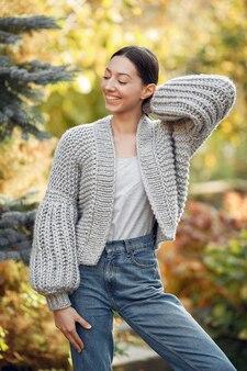 Ragazza in un maglione grigio che posa all'aperto