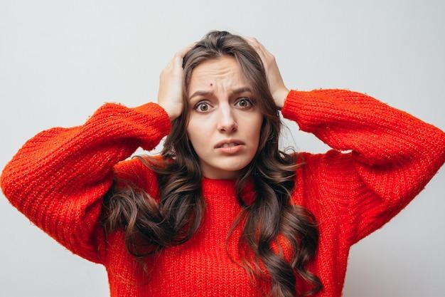 Ragazza in un maglione rosso tiene la testa a causa di stress.