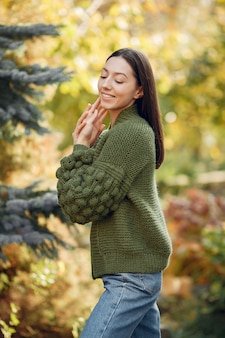 Ragazza in un maglione verde che posa all'aperto