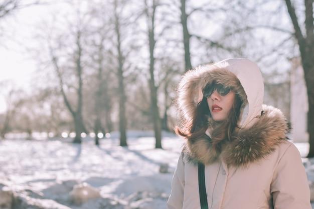 Ragazza in un parco di inverno nel pomeriggio in precipitazioni nevose