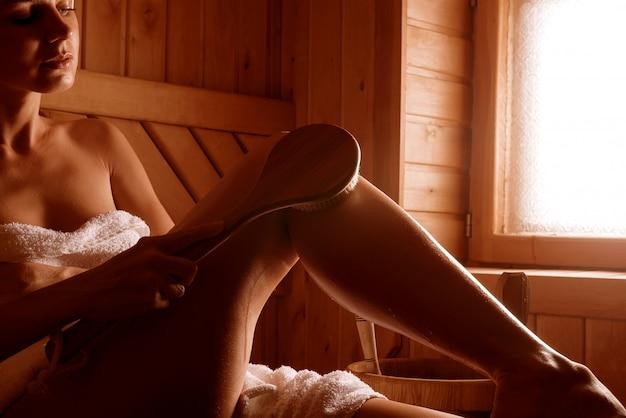 Ragazza in un trattamento termale in una sauna tradizionale con un pennello per la pelle e un asciugamano.