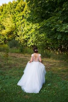 Ragazza in un vestito bianco nel prato. donna in un bellissimo abito lungo in posa nel giardino.