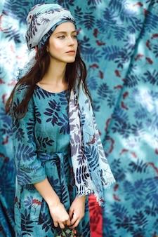 Ragazza in un vestito di lino. con una corona di fiori in testa.