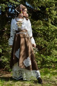 Ragazza in un vestito fatto a mano di moda etnica vintage in posa all'aperto, insolito costume retrò sul corpo della ragazza