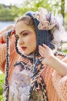 Ragazza in un vestito fatto a mano di modo etnico d'annata che posa all'aperto. insolito costume retrò sul corpo della ragazza, sorriso ed emozioni allegre. ,