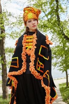 Ragazza in un vestito fatto a mano di modo etnico d'annata che posa all'aperto
