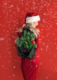 Ragazza in un vestito rosso con cappello santa con uno zaino fuori dal quale sporgono i rami di un albero di capodanno