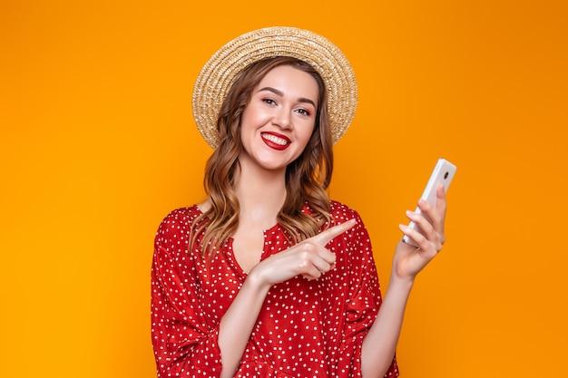 Ragazza in un vestito, un cappello di paglia tiene un telefono cellulare e punta un dito contro di lui isolato su sfondo arancione