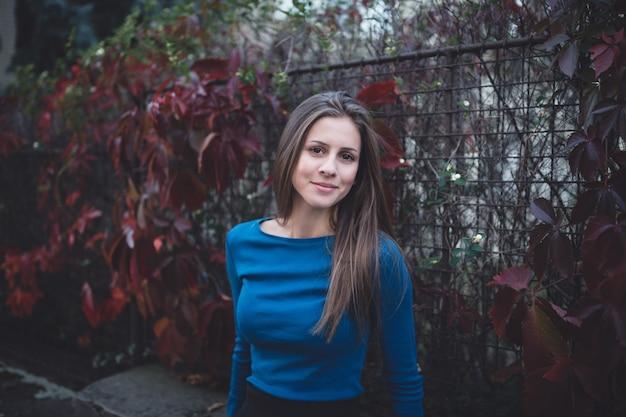 Ragazza in una camicia a maniche lunghe blu sulla strada. tempo di autunno.