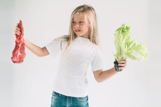 Ragazza in una camicia bianca che tiene carota e carne cruda