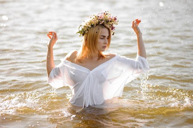 Ragazza in una camicia bianca con trasparenza e corona floreale in piedi in acqua