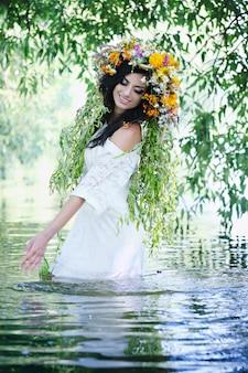 Ragazza in una corona che spruzza in acqua