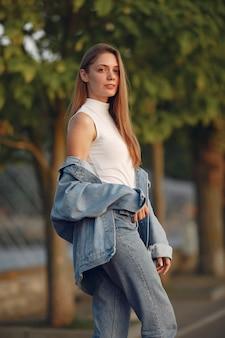 Ragazza in una giacca di jeans blu in una città estiva