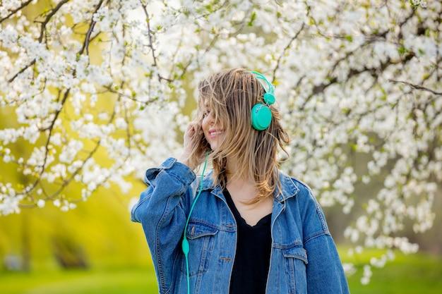 Ragazza in una giacca di jeans e cuffie si trova vicino a un albero in fiore