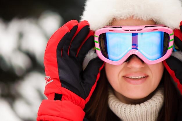 Ragazza in una giacca sportiva rossa nella foresta invernale sci,