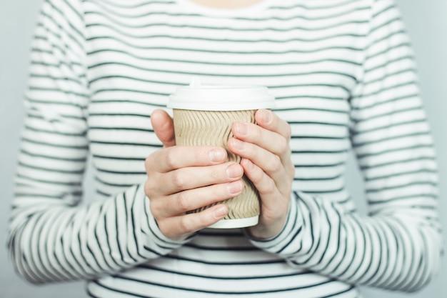 Ragazza in una maglietta a strisce tiene una tazza di carta con caffè o tè davanti a lei.